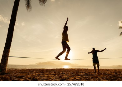 teenagers balance slackline on sunrise beach silhouette