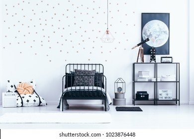Teenager's bed next to a shelf with telescope against white wall with gold stars and moon poster in bedroom interior