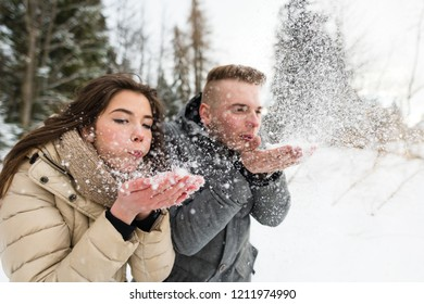 Teenagers blowing snow on mountains