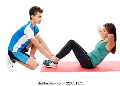Teenagers boy and girl helping each other working out abs crunches on a mat