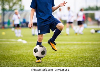 Teenagers Boys Playing Soccer Football Match. Young Football Players Running and Kicking Soccer Ball on a Soccer Pitch.