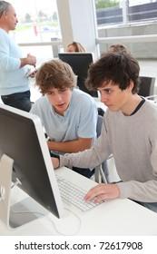 Teenagers in classroom working on desktop computer