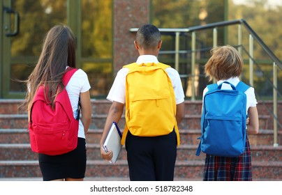 Teenagers with colourful backpacks on school entrance background