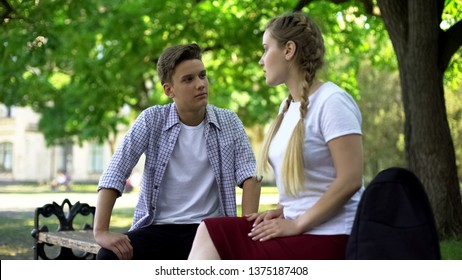 Teenagers couple conflicting, sitting at park bench, conflict based on jealousy