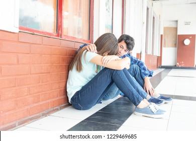 Teenagers couple at school. Boy conforting sad girl.