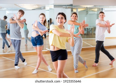 Teenagers in dance hall studying new movements, smiling and having fun
