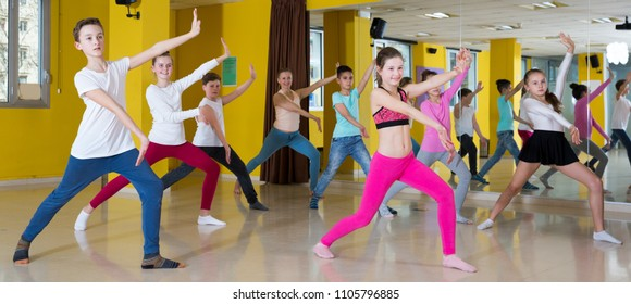 Teenagers dancers practicing dance routine with female choreographer in modern studio