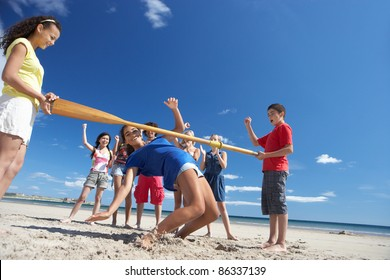 Teenagers doing limbo dance on beach
