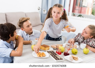 Teenagers friends eating sweet food with tea at the table on sofa