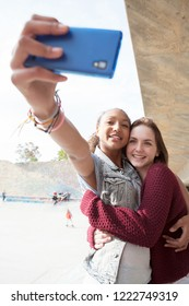 Teenagers friends hugging using smartphone to take selfies photos, smiling in skateboarding park, networking social media outdoors. Diverse students using technology, leisure recreation lifestyle.