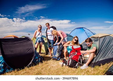 Teenagers in front of tents packing, summer music festival