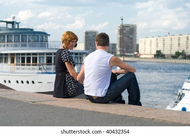 Teenagers: girl and fellow are in harbor. Look against each other. Loving couple