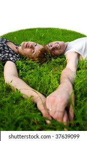 Teenagers: girl and fellow are lying on green grass. Their hands together. Green grass around them