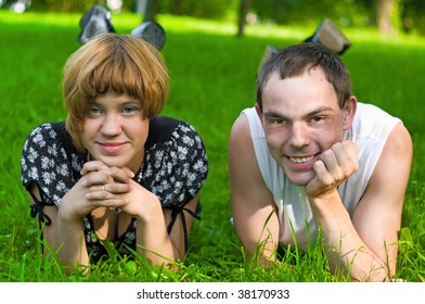 Teenagers: girl and fellow are lying on green grass. They see forward. Green grass around them
