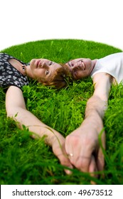 Teenagers: girl and fellow are lying on green grass. They see forward. Their hands together. Green grass around them