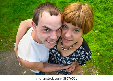 Teenagers: girl and fellow are staying on green grass and embracing. Green grass around them and flower. Fisheye