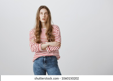 Teenagers hate when parents scolding. Bothered and annoyed european female student rolling eyes and sighing, standing with crossed arms over gray background, being bored and fed up of nonsense talks