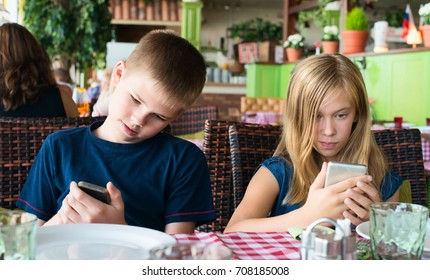 Teenagers having fun with mobile phones in cafe. Modern lifestyle and technology concept. Children sitting in restaurant and looking on the smartphones.