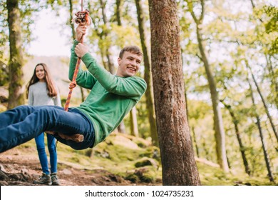 Teenagers are having fun on a rope swing which they have found while hiking.