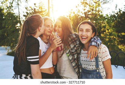 Teenagers having fun in a park while drinking a beverage