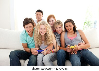 Teenagers having fun playing video games in the living-room