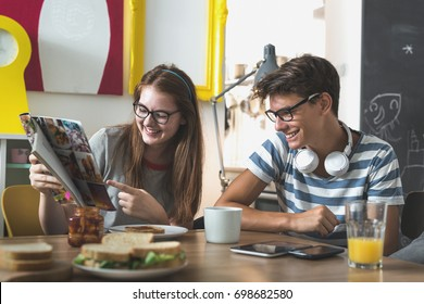 Teenagers having fun reading magazine at their home