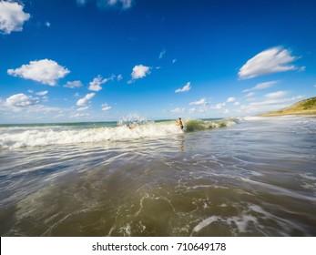 teenagers having fun in the sea waves - summertime - Sicily mediterranean sea