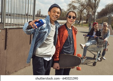 teenagers having fun with shopping cart in skateboard park, hipster style concept
