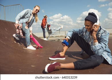 teenagers having fun in skateboard park, hipster students concept