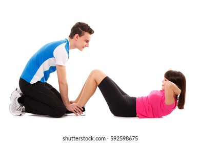 Teenagers helping each other do abs crunches