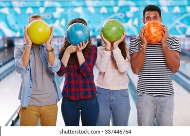 Teenagers hiding their faces behind bowling balls