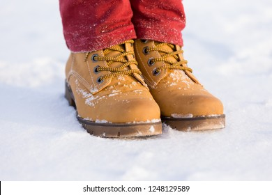 Teenager's legs at the yellow boots standing on the snow, closeup