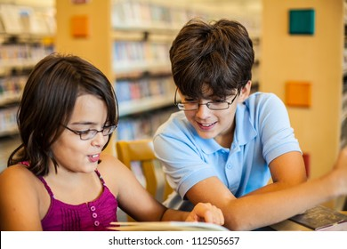 Teenagers in a library are reading a book