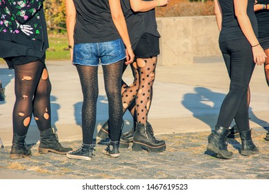 Teenagers Lifestyle. Casual Youth Subculture Style Concept. Group of trendy young girls wearing holey tights and shabby boots on street of big city.