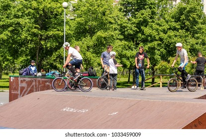 Teenagers on bicycles. St. Petersburg, Russia - 15 June, 2017. Teenagers on bicycles in the park at sports facilities.