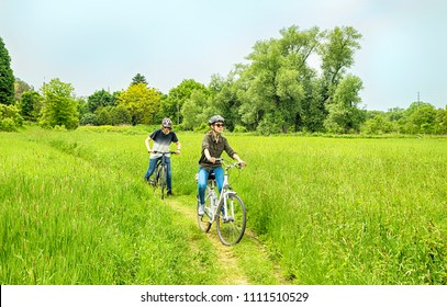 Teenagers on their bikes in meadow trail. Young girl and man on their bikes in meadow trail.  Cycle ride in countryside