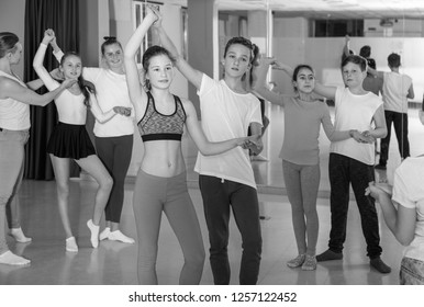 Teenagers in pairs learning to dance active boogie-woogie with female choreographer in modern studio