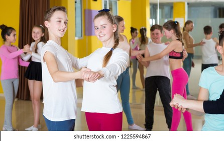 Teenagers in pairs learning to dance waltz with female choreographer in modern studio