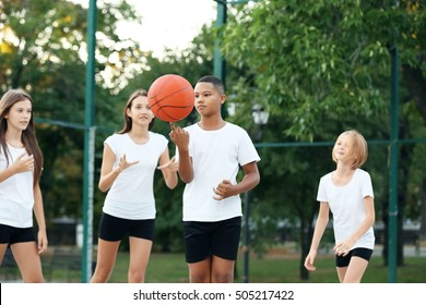 Teenagers playing basketball on school yard