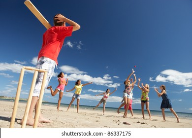 Teenagers playing cricket on beach