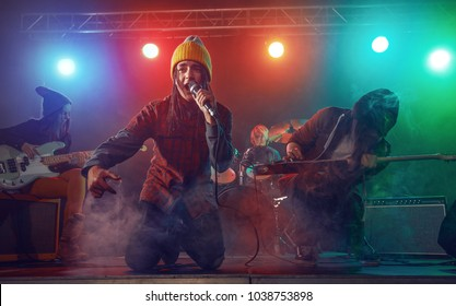 Teenagers are playing rock. Stage light, smoke.