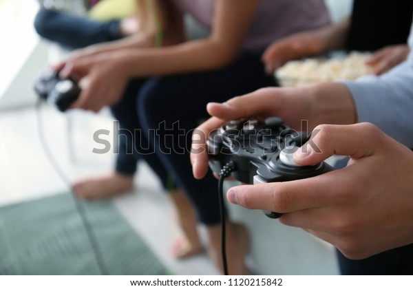 Teenagers playing video games at home, closeup