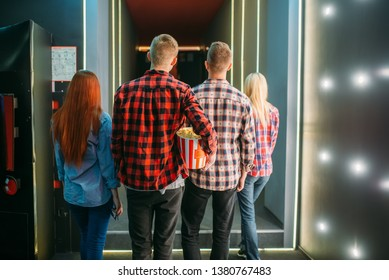 Teenagers with popcorn stands in cinema hall