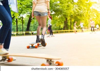 Teenagers practicing long board riding outdoors in skateboarding park. Active urban life. Urban subculture. Copy space.