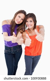 Teenagers putting their thumbs up with beaming smiles
