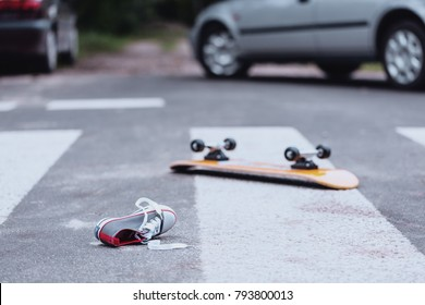 Teenager's shoe and skateboard lying on a pedestrian crossing after traffic accident