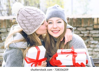 Teenagers sisters exchanging present and kissing outdoors at winter season - Best female friends hugging at park holding gift looking at camera and smiling - Concept of friendship holidays and love