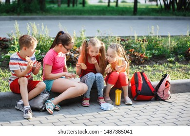 Teenagers sit and eat on the sidewalk curb in the city park.