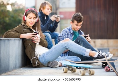 teenagers with smartphones in autumn day outdoors