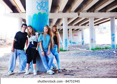 Teenagers standing at the column marked with graffiti